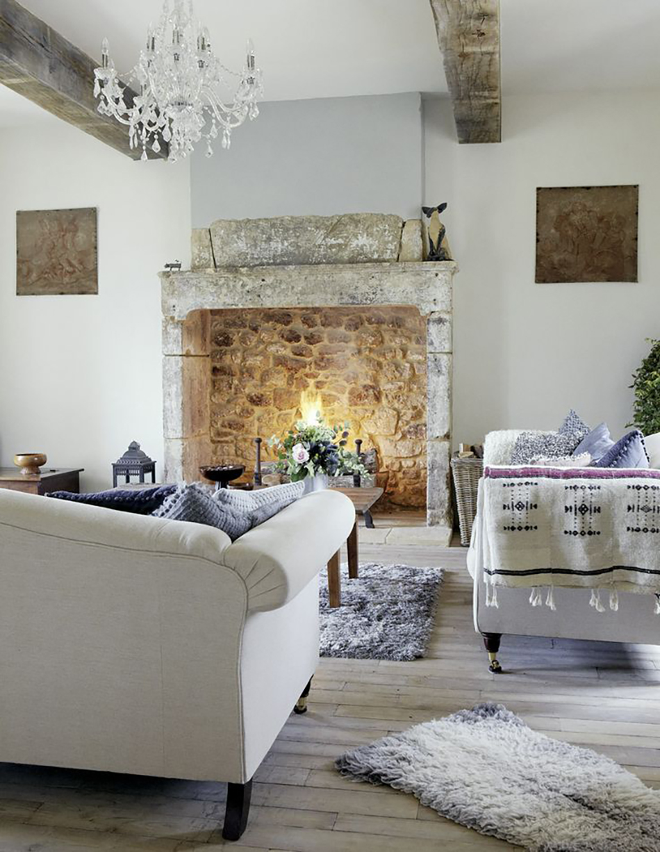 White living room, oak wood ceiling beams, rustic vintage table, comfy grey sofa, lilac rug, wood flooring, stone fireplace, lit fire CH&I 02/2011 not used